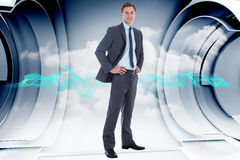Composite image of smiling businessman with hands on hips Stock Photo