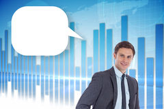 Composite image of smiling businessman with hands on hips with speech bubble Stock Photo