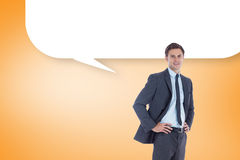 Composite image of smiling businessman with hands on hips with speech bubble Royalty Free Stock Images