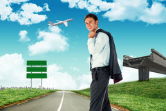 Composite image of smiling businessman holding his jacket. Smiling businessman holding his jacket against road leading out to the horizon stock photography