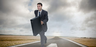 Composite image of smiling businessman in a hurry Stock Photo