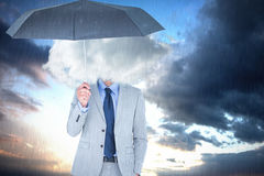 Composite image of smiling businessman looking at camera under umbrella Stock Photo
