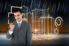 Composite image of smiling businessman looking at his cellphone Stock Photo