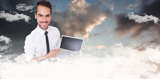 Composite image of smiling businessman pointing his laptop Royalty Free Stock Image