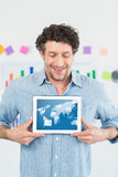 Composite image of smiling businessman showing digital tablet in creative office Royalty Free Stock Photography