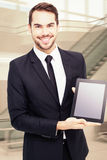 Composite image of smiling businessman showing his tablet pc Stock Image