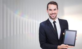 Composite image of smiling businessman showing his tablet pc Stock Images