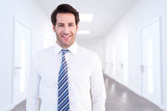Composite image of smiling businessman standing with hands in pockets Stock Photos