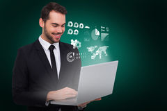 Composite image of smiling businessman standing and using laptop. Smiling businessman standing and using laptop against green background with vignette Royalty Free Stock Images
