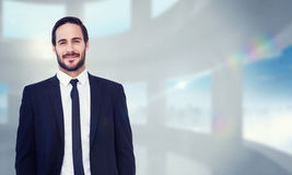 Composite image of smiling businessman in suit standing with hands in pockets Royalty Free Stock Photos