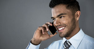 Composite image of smiling businessman talking on mobile phone Stock Image