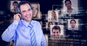 Composite image of smiling businessman using headset Royalty Free Stock Image