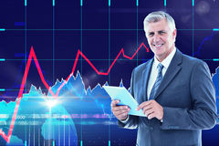 Composite image of smiling businessman using his tablet Royalty Free Stock Photo