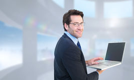 Composite image of smiling businessman using a laptop Stock Images