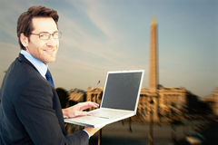Composite image of smiling businessman using a laptop Royalty Free Stock Photo