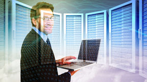Composite image of smiling businessman using a laptop Royalty Free Stock Images
