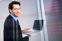 Composite image of smiling businessman using a laptop royalty free stock image