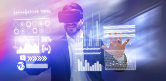 Composite image of smiling businessman using virtual reality glasses. Smiling businessman using virtual reality glasses against tables in office cafeteria Stock Photos