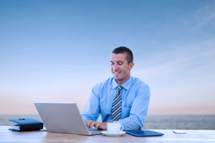 Composite image of smiling businessman working with his laptop. Smiling businessman working with his laptop against beautiful sunset on a sunny day Stock Image