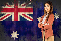 Composite image of smiling businesswoman with crossed arms. Smiling businesswoman with crossed arms against australia flag in grunge effect Stock Images