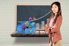 Composite image of smiling businesswoman with crossed arms. Smiling businesswoman with crossed arms against black board on a wooden shelf Royalty Free Stock Images