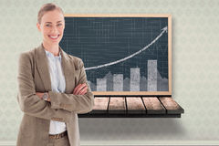 Composite image of smiling businesswoman with crossed arms. Smiling businesswoman with crossed arms against black board on a wooden shelf stock photo
