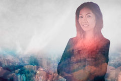Composite image of smiling businesswoman with crossed arms. Smiling businesswoman with crossed arms against new york Royalty Free Stock Image