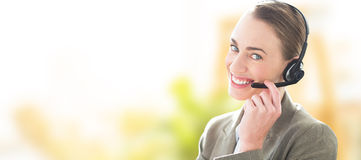 Composite image of smiling businesswoman with headset using computers Stock Photography