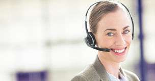 Composite image of smiling businesswoman with headset using computers Stock Image
