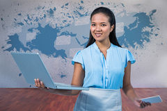 Composite image of smiling businesswoman holding smartphone and laptop Royalty Free Stock Photography