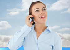 Composite image of smiling businesswoman looking upwards while on her phone Royalty Free Stock Image
