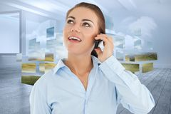 Composite image of smiling businesswoman looking upwards while on her phone Stock Photography