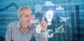 Composite image of smiling businesswoman pointing Stock Image