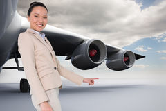 Composite image of smiling businesswoman pointing Royalty Free Stock Images