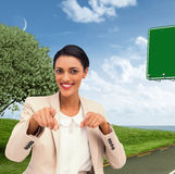 Composite image of smiling businesswoman pointing at the camera Stock Image