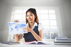 Composite image of smiling businesswoman pointing a sheet of paper Royalty Free Stock Images