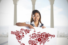 Composite image of smiling businesswoman pointing a white poster Stock Photo