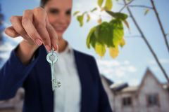 Composite image of smiling businesswoman showing new house key. Smiling businesswoman showing new house key against green and yellow leaves growing on branch Royalty Free Stock Photography