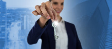 Composite image of smiling businesswoman showing new house key. Smiling businesswoman showing new house key against illuminated buildings by road in city Stock Photos