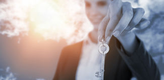 Composite image of smiling businesswoman showing new house key. Smiling businesswoman showing new house key against view of beautiful sky and clouds Stock Image