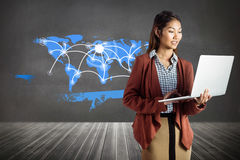 Composite image of smiling businesswoman using laptop Royalty Free Stock Images