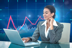 Composite image of smiling businesswoman using laptop at desk Stock Photo