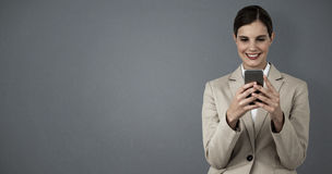 Composite image of smiling businesswoman using mobile phone Stock Images