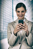 Composite image of smiling businesswoman using mobile phone Royalty Free Stock Photography
