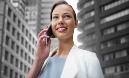 Composite image of smiling businesswoman using smart phone Royalty Free Stock Photos