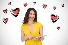 Composite image of smiling casual young woman scrolling on her tablet computer Royalty Free Stock Images