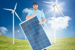 Composite image of smiling construction worker holding solar panel Stock Images