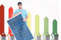 Composite image of smiling construction worker holding solar panel Royalty Free Stock Image