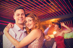 Composite image of smiling couple embracing each other in bar Royalty Free Stock Photos