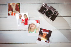 Composite image of smiling couple embracing and holding gift. Smiling couple embracing and holding gift against instant photos on wooden floor Stock Image